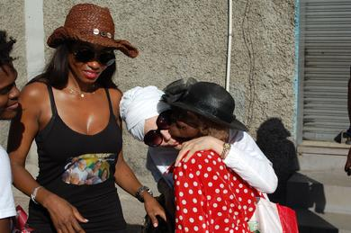 Safiyya embracing a poor elderly Jamaican woman with her partner Keturah Hamilton.