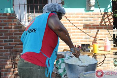 Jamaican volunteer from Feeding of the 5000 making the rice.